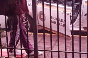 Preso é algemado em grade na calçada devido ao excesso de lotação das celas na delegacia de Taquara